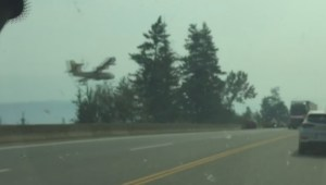 Water bomber drops water by a highway as wildfire burns near Salmon Arm, B.C.