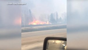 Abandoned vehicles, houses on fire line routes out of Fort McMurray