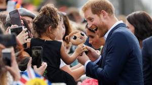 Children hand Prince Harry and Meghan Markle stuffed toys during Auckland meet and greet
