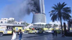 Flames and smoke still billowing in the morning at Dubai hotel