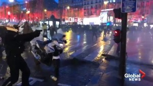 French police officer pulls gun on 'yellow vest' protesters at Champs Elysees