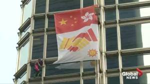 French spiderman hangs banner with 'message of peace' on Hong Kong building