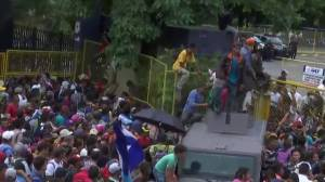 Migrants break through fence at Guatemala-Mexico border