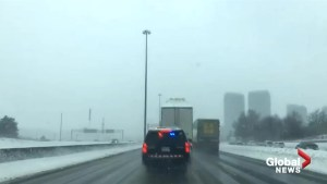Dashcam footage captures OPP pulling over truck with snow-covered roof on Hwy. 401