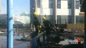 Firefighters able to reach top of London apartment building, blaze still smoldering