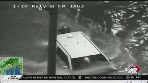 Live TV coverage spots vehicle stuck in fast moving flood waters from traffic camera, person rescued