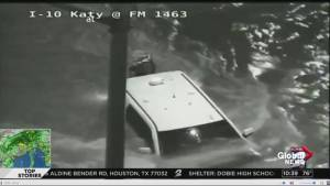 Live TV coverage spots vehicle stuck in fast moving flood waters from traffic camera, person