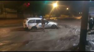 Flood waters sweep cars down roads in Peru after heavy rains