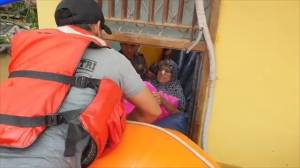 Rescuers in Indonesia save elderly woman trapped in home by floods