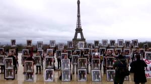 French climate activists hold Macron portraits upside down to denounce lack of action