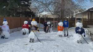Family builds hockey team of snowmen