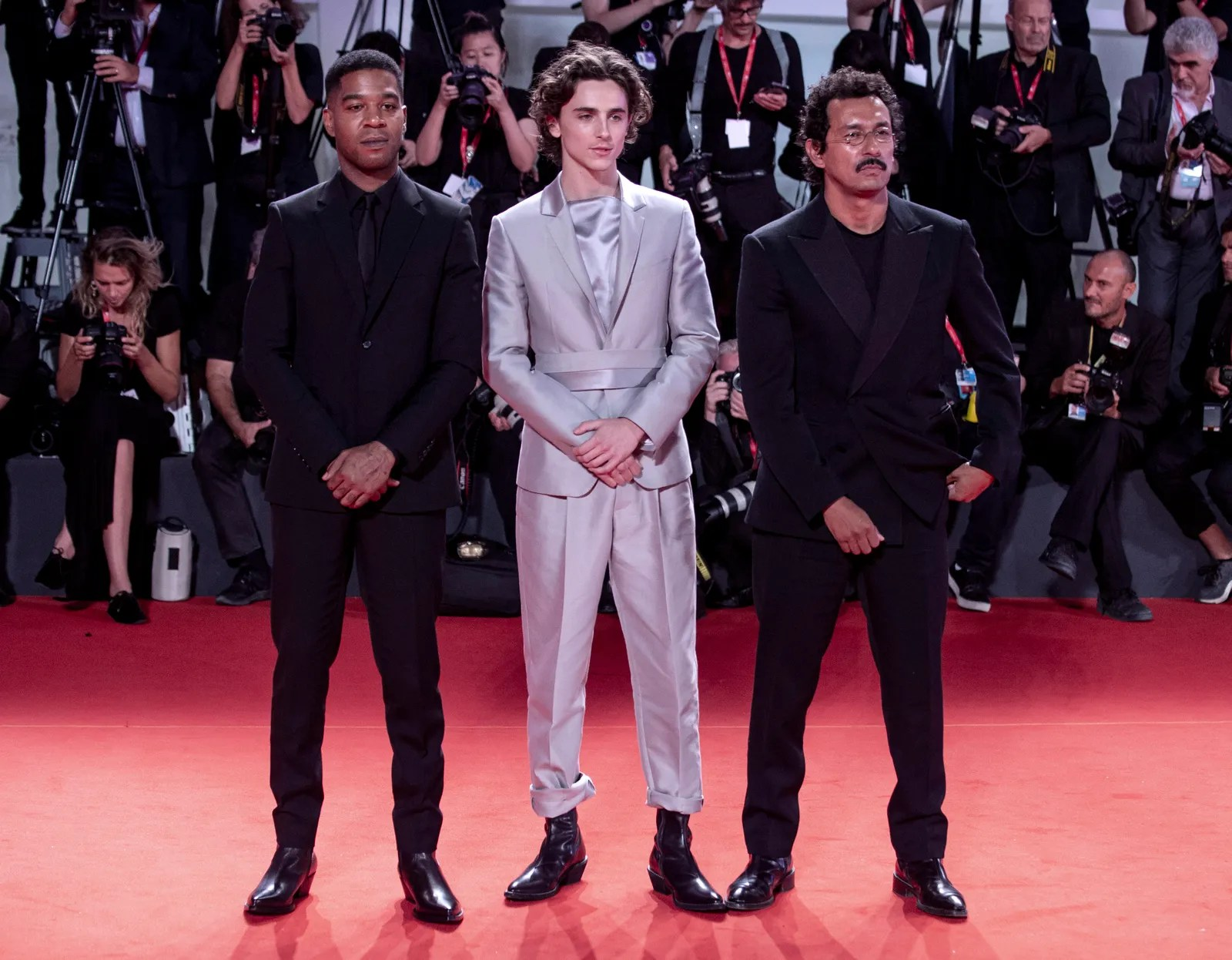3 men stand on a red carpet with a crowd in the background. 2 are wearing all black while the man in the middle wears...