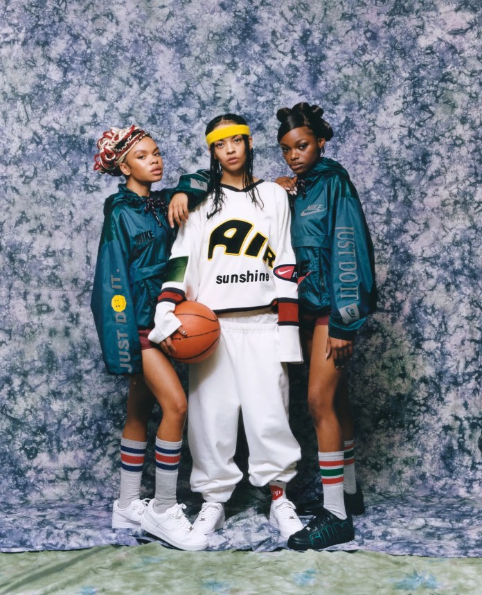 3 women wearing Nike x CPFM outfits on a blue fabric backdrop modeled to look like a school portrait from the 1980s