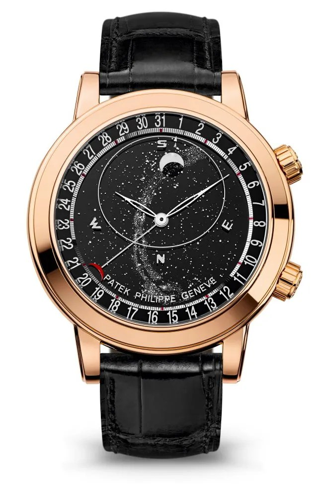 A gold watch with a black face with an illustration of the moon and stars