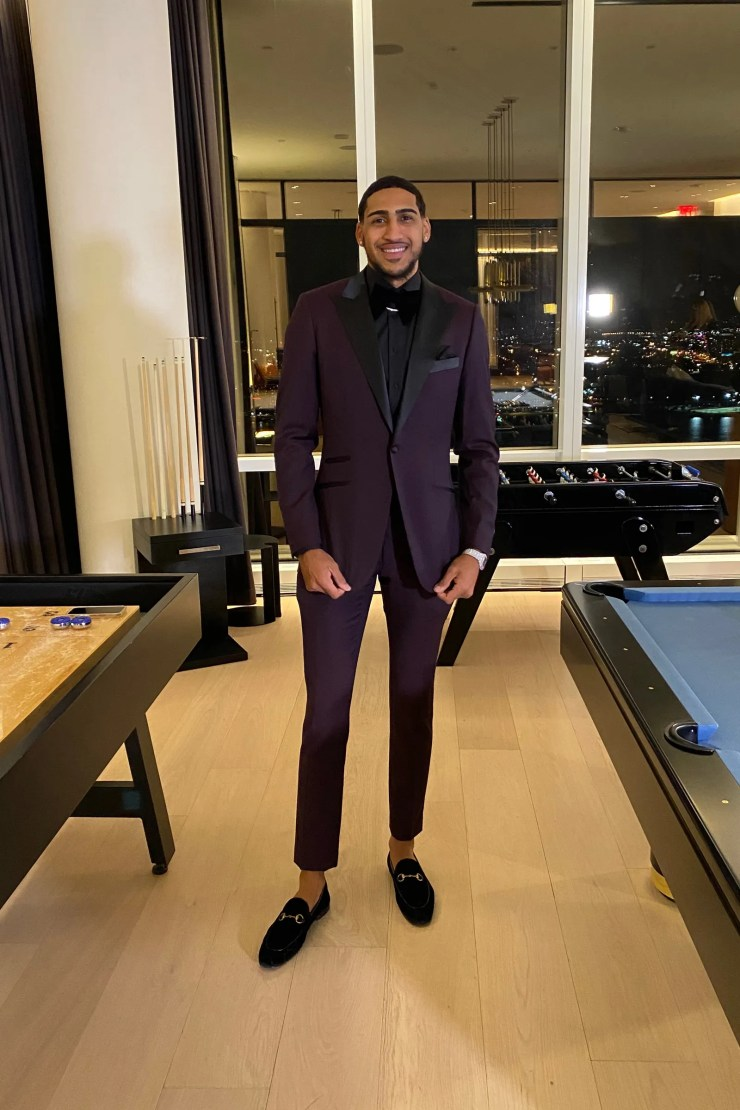 Obi Toppin wearing a maroon suit and smiling