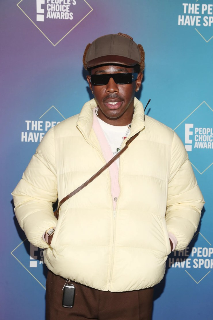 Tyler The Creator wearing a white jacket and brown pants with sunglasses at an awards show