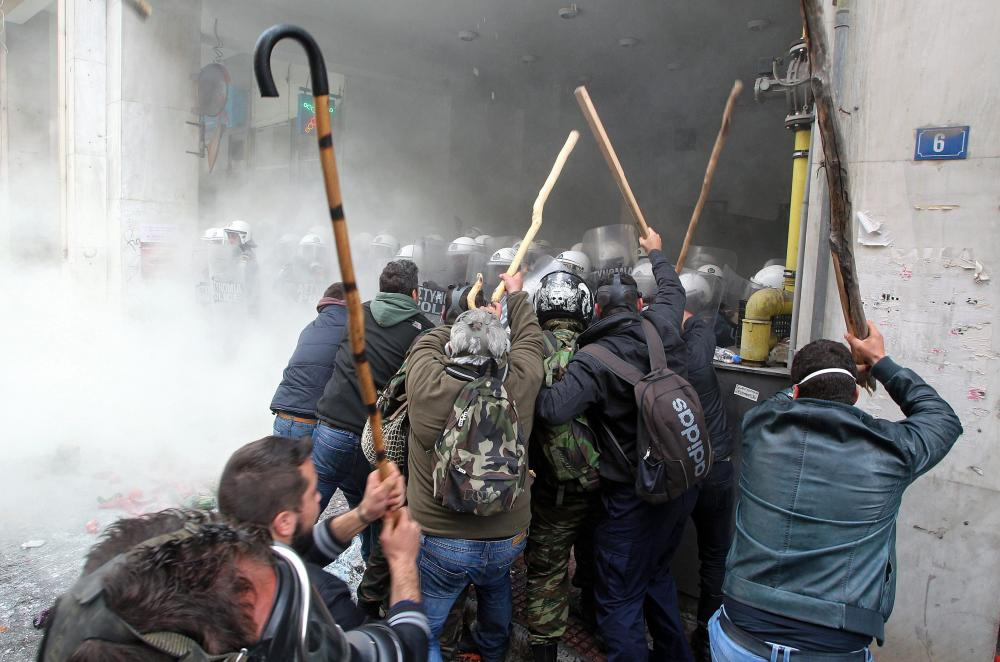 Farmers clash with riot policemen outside the Agriculture Ministry in Athens, Greece, 12 February 2016. Farmers from all over Greece organise a massive protest in central Athens requesting that the government withdraws its proposed social security and pension reform plan. Protesters are expected to meet in Athens and walk towards the Parliament on Syntagma square, where they will set up tents to house farmers who will remain there for the entire weekend. EPA/PANTELIS SAITAS