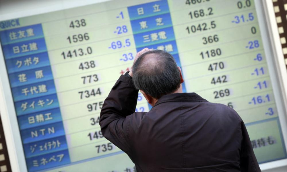 A man scratches his head as he looks at an electronic stock board showing Japan's Nikkei 225 in Yokohama, near Tokyo, Wednesday, Feb. 10, 2016. Asian stock markets fell for a third consecutive day Wednesday, beset by nerves about shaky global growth, falling oil prices and possible capital shortfalls at major European banks. (AP Photo/Eugene Hoshiko)