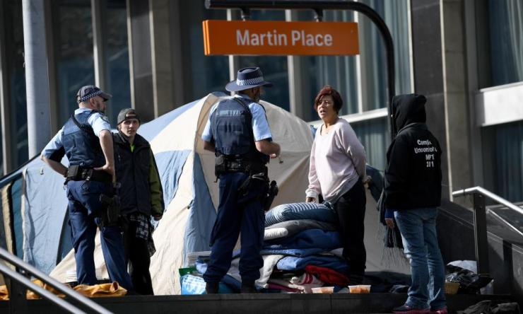 Homeless people speak to police as they pack their belongings on Friday.