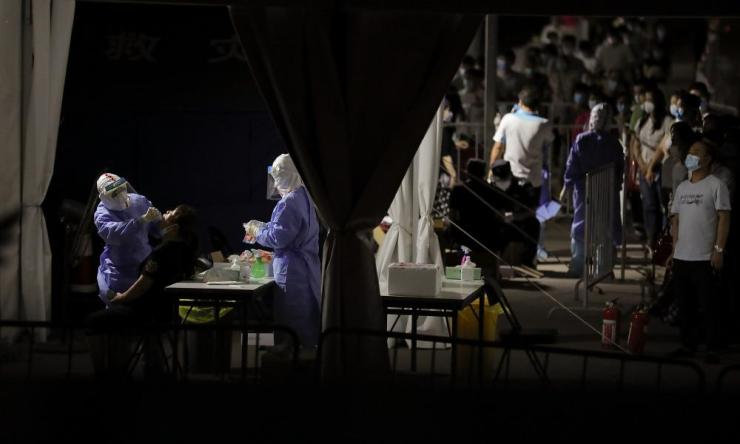 A nurse wearing a protective suit and mask takes a nucleic acid test for Covid-19 from a person who either visited or lives near the Xinfadi Market at a testing facility at a Sport Center on 17 June 2020 in Beijing, China.