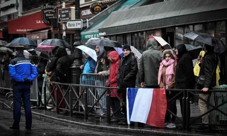 Parisians wait for the hearse transporting the coffin containing the body of Arnaud Beltrame.