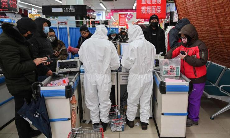 Pharmacy workers wearing protective clothes and masks serve customers in Wuhan on January 25, 2020.
