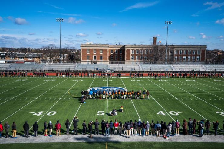 Eastern High School students walk out of class and assemble on their football field in Washington, DC.