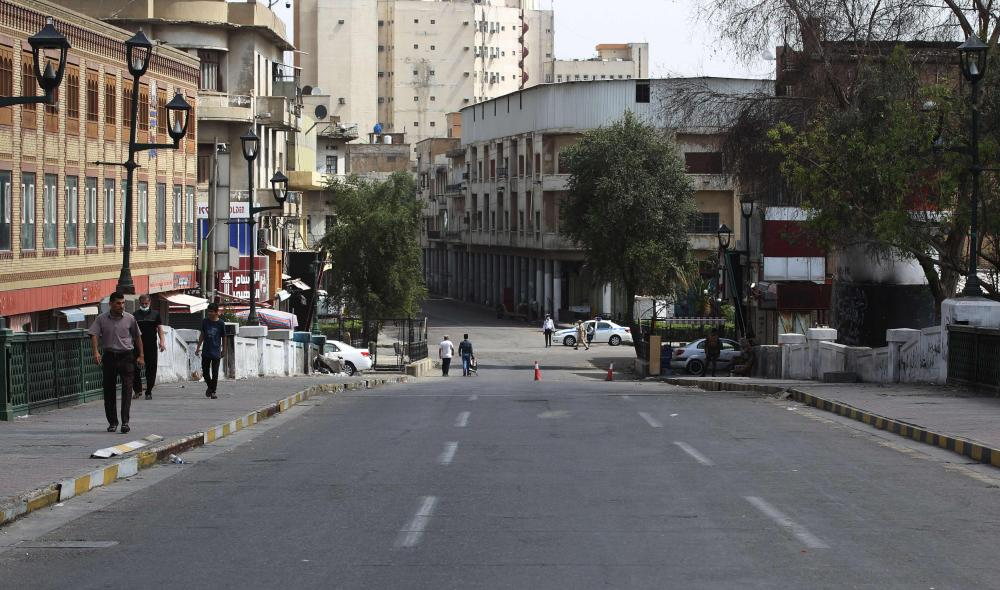 Iraqis pictured on Wednesday walking in an empty street where months before anti-government protests were taking place, during the lockdown to contain the spread of the coronavirus