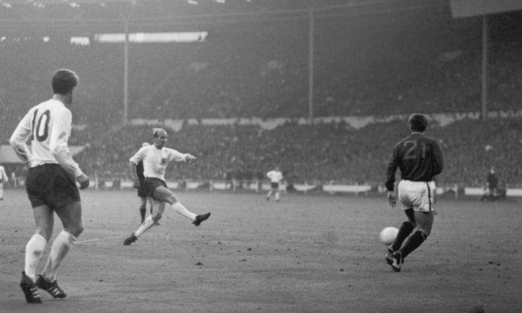 Bobby Charlton belts England's second. Geoff Hurst, having teed him up, looks on.