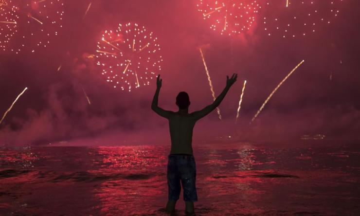 A man watches fireworks exploding over Copacabana beach.