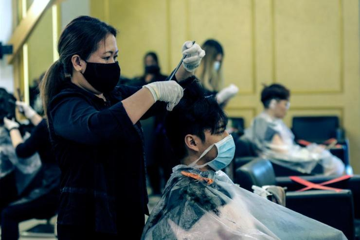A woman cuts hair at a salon in Kuala Lumpur.