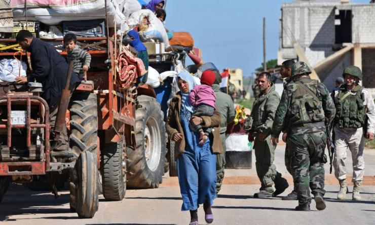 Displaced Syrian families arrive at a checkpoint