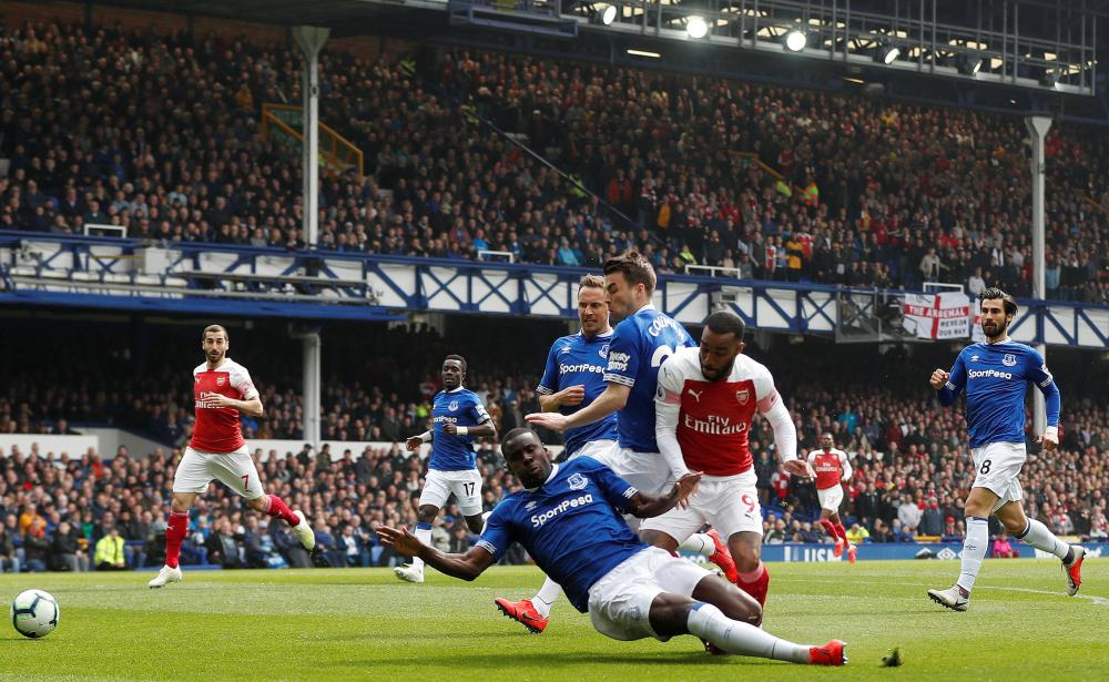 Zouma tackles Lacazette as he shoots.