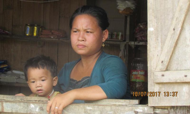 A mother and child survey scenes of devastating flooding in north-east India