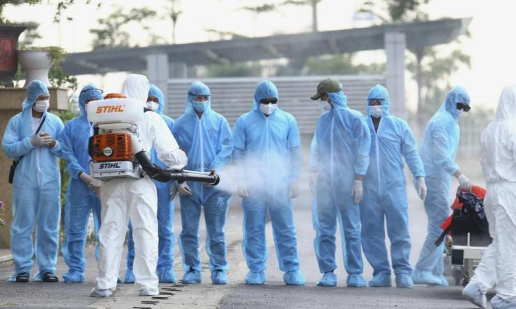 A health worker disinfects arriving Vietnamese patients at the national hospital of tropical diseases in Hanoi, Vietnam. The 129 patients who were working in Equatorial Guinea were brought home in a repatriation flight for treatment for the coronavirus.