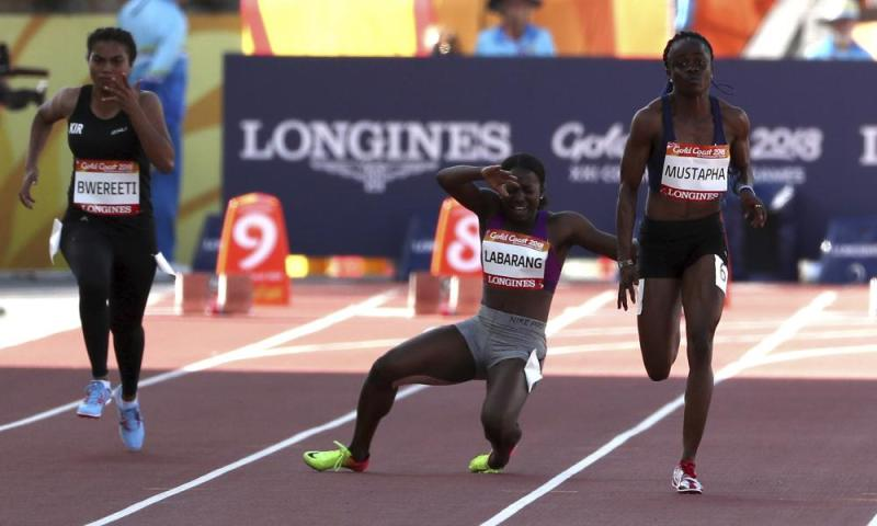 Charifa Abdoullahi Labarang of Cameroon collapses during her heat of the women's 100m.