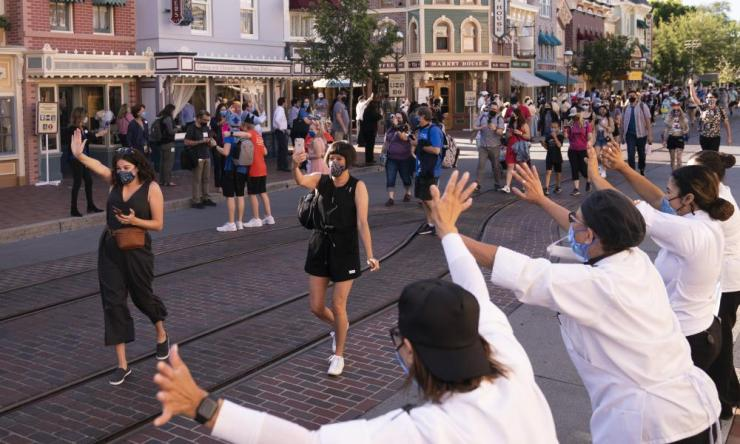 Employees wave at guests at Disneyland in Anaheim, California after the theme park opened its gates and some visitors came in cheering and screaming with happiness.