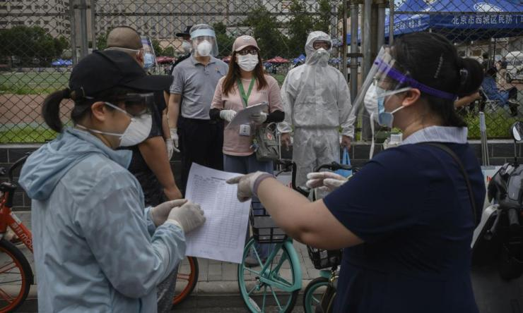 A Chinese epidemic control worker wears a protective suit and mask as he and volunteers direct and register people preparing for Covid-19 tests.