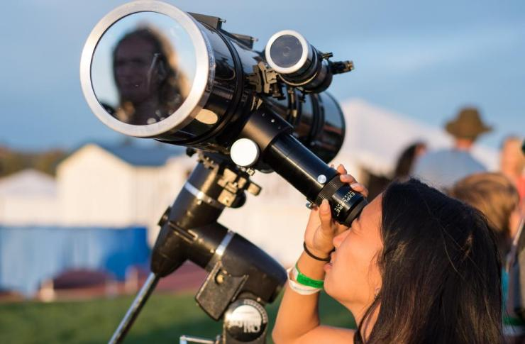 A woman looks through a telescope at the sun the evening before the total solar eclipse in Madras, Oregon.