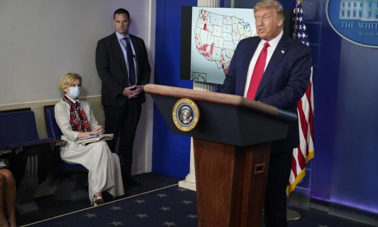 White House coronavirus response coordinator Dr. Deborah Birx, left, listens as President Donald Trump speaks during a news conference in Washington.