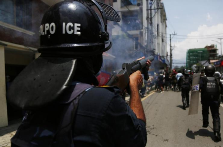 Nepalese police officer fires teargas towards demonstrators in Kathmandu, Nepal, on Thursday.