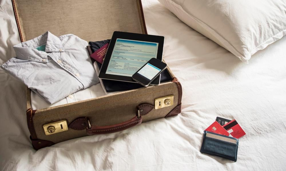 suitcase with clothes and digital tablet