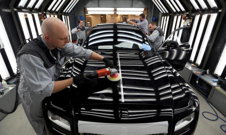 A team of employees polish the exterior bodywork of a Ghost automobile at the Rolls Royce Motor Cars Ltd. plant in Goodwood, UK.