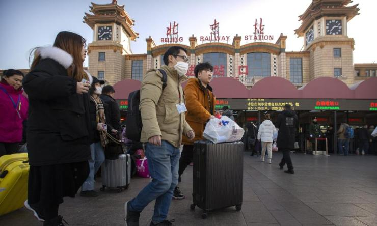 A traveller wears a face mask outside Beijing railway station