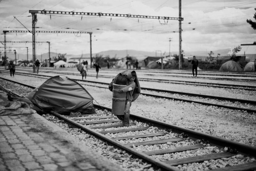 A boy carries his belongings on the day the Greek military began evicting people from the Idomeni refugee camp
