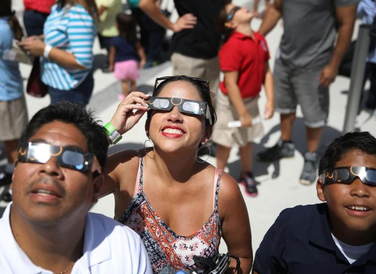 Alex Gamarra and Jessica Gamarra (L-R) view the solar eclipse at The Phillip and Patricia Frost Museum of Science in Miami, Florida.