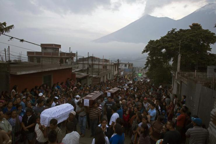 People carry the coffins of seven people who died during the eruption of the Volcan de Fuego.