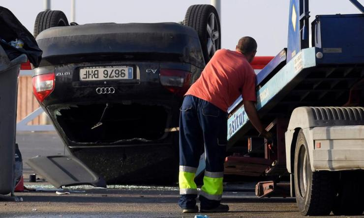 An employee starts to tow away a car involved in a terrorist attack in Cambrils, a city 120km south of Barcelona.