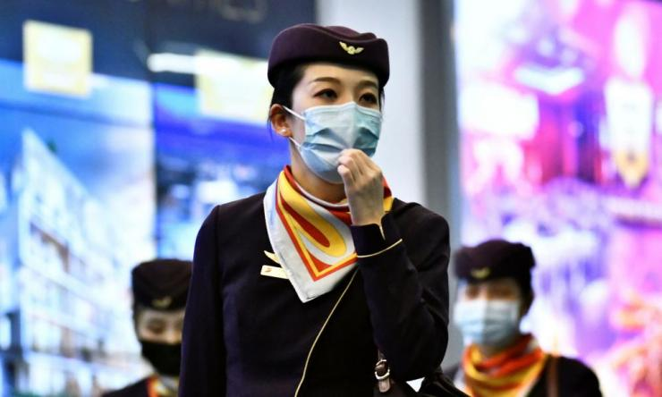 Flight crew wearing masks arrive on a direct flight from China at Vancouver International Airport