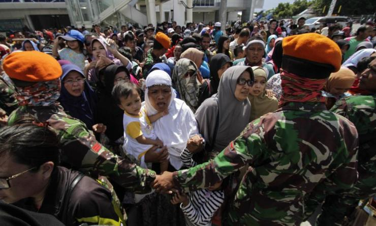 Residents queue to board a Hercules aircraft belonging to the Indonesian Air Force, as they are being evacuated from Palu